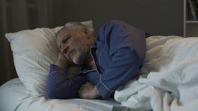 Серый с волосами человек лежа в кровати и страдая от инсомнии, депрессии и здоровья стоковые фото