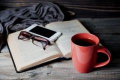Серый уютный связанный шарф с чашкой кофе или чаем, телефоном, стеклами и открытой книгой на деревянном столе Стоковые Изображения
