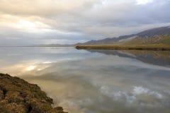 Серый цвет заволакивает отражение в ровной поверхности зеркала озера mountaim стоковое изображение