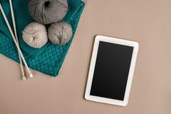 Серый цвет и шерсти бирюзы вязать, вязать иглы и таблетка с черным экраном на бежевой предпосылке Взгляд сверху экземпляр Стоковая Фотография
