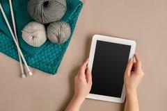 Серый цвет и шерсти бирюзы вязать, вязать иглы и таблетка с черным экраном на бежевой предпосылке Взгляд сверху экземпляр Стоковое Изображение RF