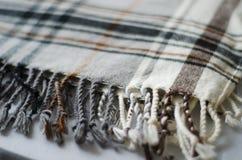Серый цвет и biege checkered связали сложенный край одеяла Стоковая Фотография RF