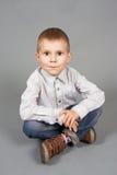 серый цвет мальчика предпосылки сидит Стоковое Изображение