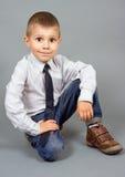 серый цвет мальчика предпосылки сидит Стоковая Фотография