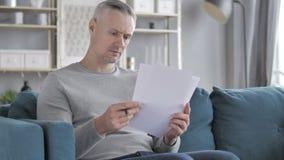 Серый человек волос читая документы пока сидящ на софе, обработке документов