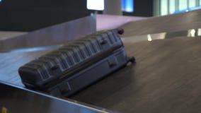 Серый чемодан на конвейерной ленте багажа в крупном аэропорте видеоматериал