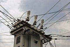Серый электрический трансформатор и высоковольтные провода стоковые фото