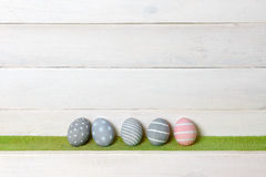 4 серых и одних розовых красочных стойки пасхального яйца handmade в ряд на зеленой лужайке на фоне деревянной поверхности с Стоковая Фотография