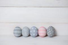 4 серых и одних розовых пасхального яйца на деревянной предпосылке С ретро влиянием фильтра Стоковое Изображение RF