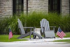 2 серых стуль Adirondack сидя на малом патио с таблицей между ими перед высокорослой декоративной травой и окнами утеса стоковое фото rf