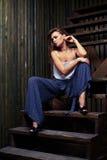 Серьга заботливой молодой девушки брюнет касающая изолированная на древесине Стоковая Фотография