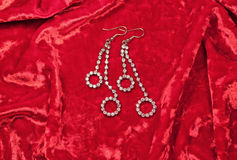 Серьги женщины на красной предпосылке бархата Стоковые Изображения