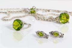 Серьги, кольцо и шкентель конца-вверх серебряные с peridot на цепи и кольце предпосылки на белом акриловом столе Стоковое Фото