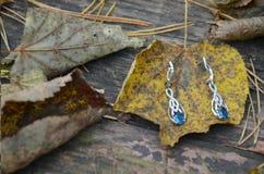 Серьги jewelry с топазом или сапфиром большой голубой камень на винтажной предпосылке Осень Листья стоковое фото rf