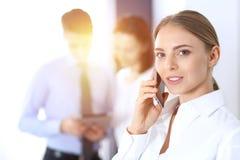 Серьезная белокурая коммерсантка говоря телефоном на заднем плане ее коллег в офисе владение домашнего ключа принципиальной схемы стоковая фотография