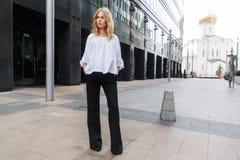 Серьезная белокурая женщина стоя полностью рост на городе улицы Стоковые Изображения