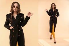 Серьезная бизнес-леди в черный представлять пальто и стекел стоковая фотография