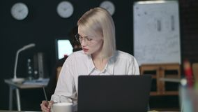 Серьезная бизнес-леди работая с финансовым документом в последнем офисе видеоматериал