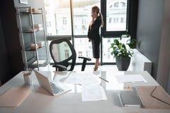 Серьезная девушка говоря телефоном в офисе стоковые фото