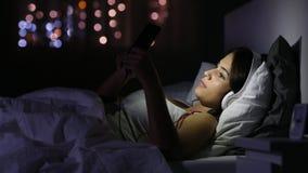 Серьезная девушка с наушниками просматривая средства массовой информации в телефоне сток-видео