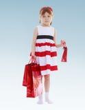 Серьезная девушка держа сумки подарка Стоковые Изображения