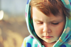 Серьезная девушка Милая маленькая девочка при серьезная сторона смотря вниз Портрет крупного плана с малой глубиной поля запачкан Стоковое фото RF
