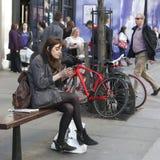 Серьезная девушка при длинные волосы сидя на стенде около Ковент Гардена Стоковое фото RF