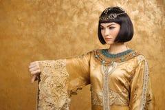 Серьезная египетская женщина как Cleopatra с большими пальцами руки вниз показывать, на золотой предпосылке Стоковые Изображения RF