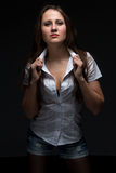 Серьезная женщина в рубашке смотря камеру стоковое изображение
