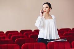 серьезная женщина говорит серьезно над телефоном стоковая фотография
