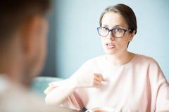 Серьезная женщина говоря к коллеге Стоковая Фотография