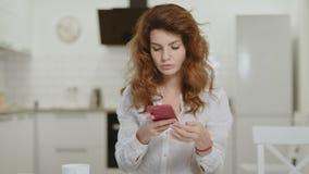 Серьезная женщина принимая телефон на открытую кухню Ноутбук молодой дамы заключительный дома видеоматериал