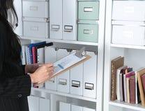 Серьезная женщина работая с цифровой таблеткой над предпосылкой файлов Стоковая Фотография RF
