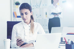 Серьезная женщина смотря телефон в офисе Стоковые Изображения RF