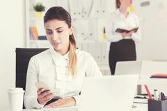 Серьезная женщина смотря телефон в тонизированном офисе, Стоковые Изображения RF