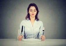 Серьезная женщина с вилкой и нож сидя на таблице с пустой плитой Стоковое фото RF