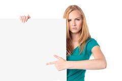 Серьезная женщина указывая к пустому знаку стоковое изображение rf
