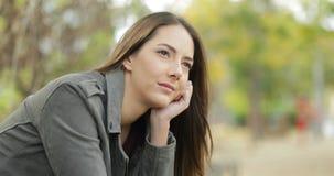 Серьезная задумчивая женщина смотря прочь в парке сток-видео