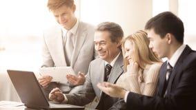Серьезная команда дела с планшетами, документами имея обсуждение в офисе Стоковое Фото