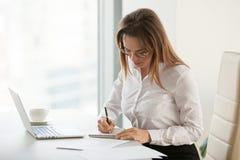 Серьезная коммерсантка принимая примечания во время по заведенному порядку утра офиса стоковое фото