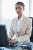 Серьезная коммерсантка работая на ее компьютере стоковое фото rf