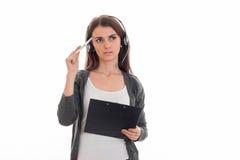 Серьезная маленькая девочка в наушниках смотрит в расстояние и derdit в руках бумаги таблетки Стоковое фото RF