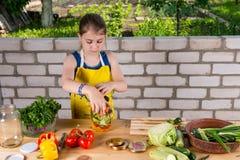 Серьезная маленькая девочка разливая свежие овощи по бутылкам стоковое изображение