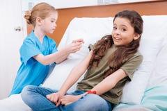 Серьезная медсестра девушки делая впрыску к пациенту в больнице Стоковые Фото