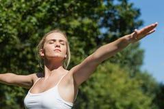 Серьезная мирная женщина делая йогу в парке Стоковое фото RF