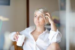 Серьезная молодая белокурая женщина сидя в ее комнате смотря задумчиво в открытом окне Красивый свет утра осветил Стоковые Изображения RF