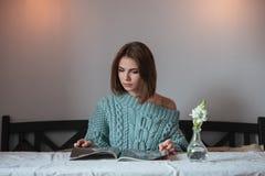 Серьезная молодая дама в кассете чтения кафа Стоковая Фотография