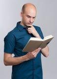 Серьезная облыселая тетрадь чтения человека Стоковые Фотографии RF