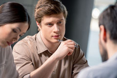 Серьезная ручка удерживания молодого человека и смотреть коллеги на деловой встрече Стоковое фото RF