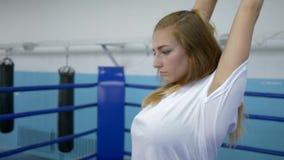 Серьезная спортсменка в перчатках бокса нагревает перед встречей боя на кольце в спортзале видеоматериал